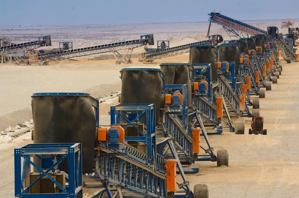 An intricate system of mobile and flexible equipment and conveyors is required to move the ore from an open pit to the leach pad